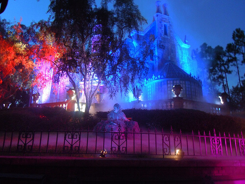 Haunted Mansion lit for Halloween (with spirit on the lawn)