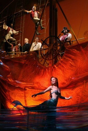 """""""I'll tell you a tale of the bottomless blue."""" Ariel (Sierra Boggess) floats on the surface just in front of Prince Eric's ship."""