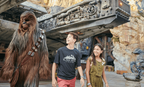 kids walking with chewbacca by the millennium falcon at galaxy's edge