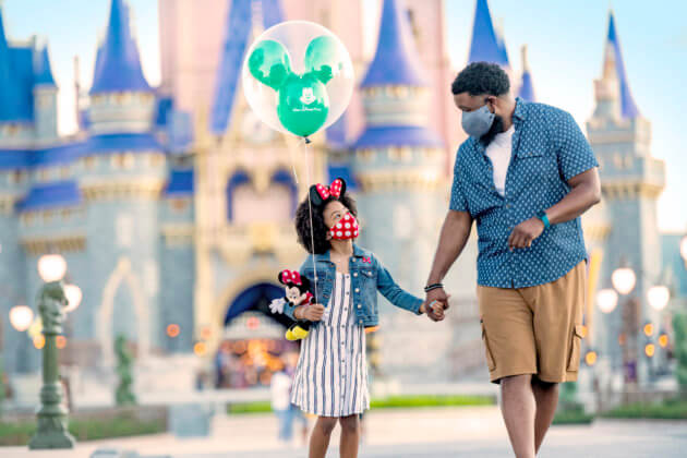 father and daughter wearing masks in front of cinderella castle at disney world