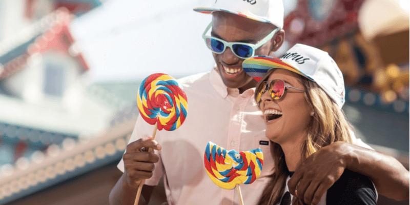 couple on pixar pier eating lollipops