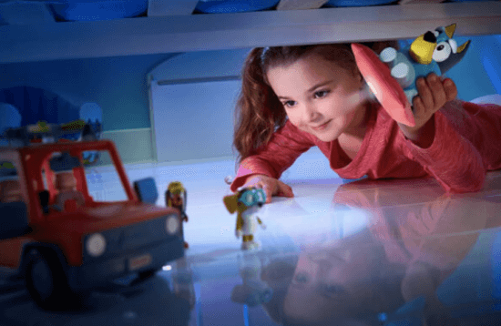 little girl playing with disney junior bluey toys