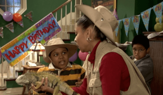 Raven holding an iguana with Cory Baxter looking at her