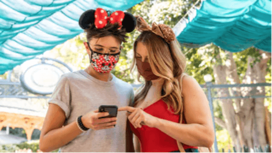 two Guests looking at the Disney App