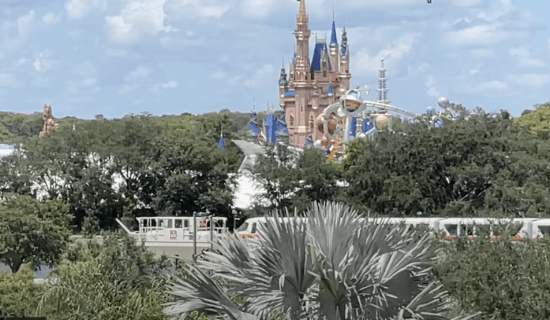 tow truck tows in orange monorail line in front of magic kingdom