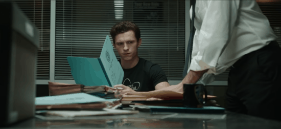 Peter Parker at a desk with a character in a white shirt and black tie leaning over