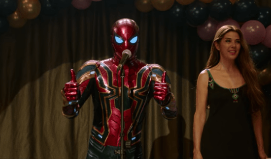 Spiderman with thumbs up talking into a microphone and May Parker