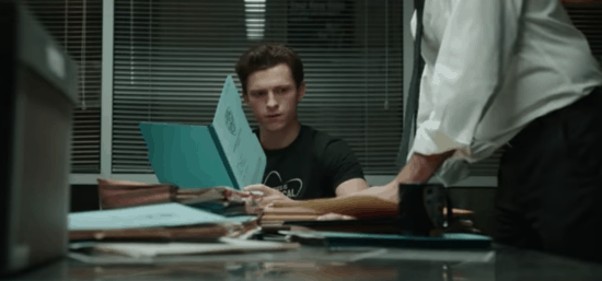 Tom Holland at a desk with a character placing files down