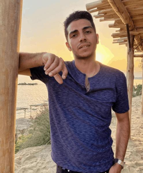 Mena Massoud on a beach