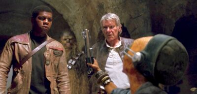 Maz Kanata handing Finn a lightsaber with Han Solo and Chewbacca surrounding him